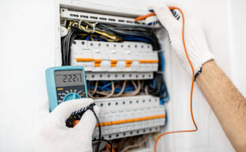 Electrician installing or repairing apartment electrical panel, close-up view