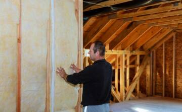 Worker thermally insulating a house attic using mineral wool installation of insulation in the house insulation of the house
